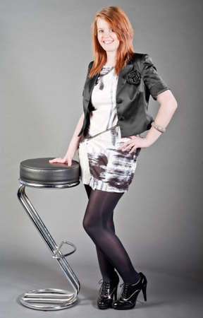 barstool: Attractive young woman standing against a stylised stool