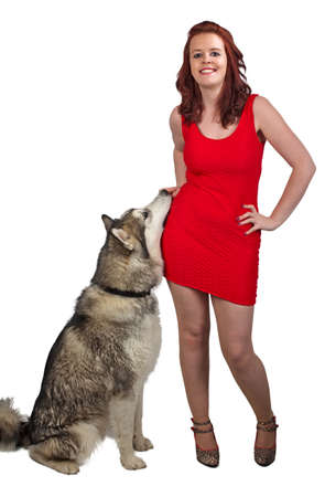 Young woman in a red dress stood next to her wolf like dog photo