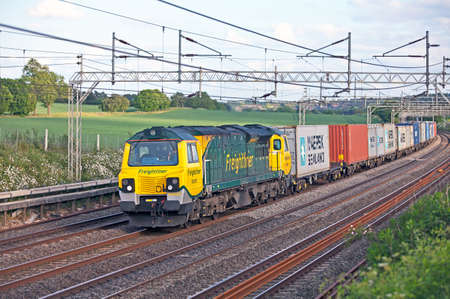 intermodal: Tring,United Kingdom,May 20 2011. Latest class addition to UK rail network (number 70007) passes north with an intermodal freight train Editorial