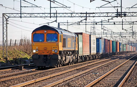 7311. Cheddington (UK) a class 66 diesel locomotive passes northward with an intermodal freight train. The UK rail freight industry has shown a 16.6% rise in volume for Q1 2011 compared to the same period in 2010 Editorial
