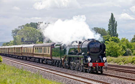 bygone: Luxurious travel. Mainline steam train taking passengers on a day trip in very high class luxurious carriages