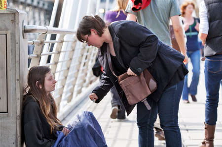 London, April 2010. A passer by stops to give money to a young homeless woman on Charing Cross bridge in London on April 25, 2010. On any given night it is estimated that 200-300 people sleep rough in London