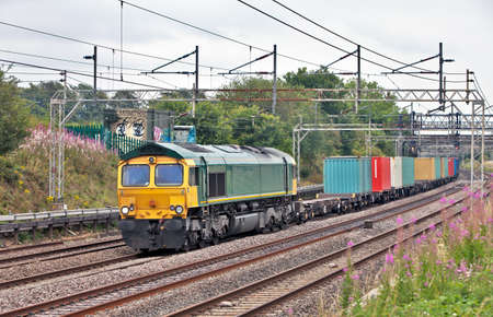 goods train: Modern diesel loco with a nortbound intermodal freight train Stock Photo