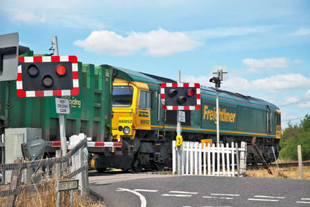 freightliner: TERRICK,ENGLAND- JULY 14: A London waste Freightliner train passes over a level crossing on July 14, 2011 at Terrick. Ninety-five percent of UK accidents at level crossings are due to pedestrian or auto driver misuse  Editorial