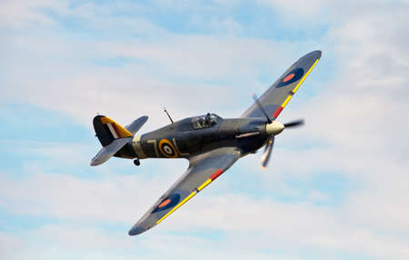 OLD WARDEN, UNITED KINGDOM - AUGUST 2011 - Hawker Hurricane Z7015 gives a low level aerial display at the Shuttleworth summer air gala on August 7, 2011 at Old Warden. This example is one of only three remaining Sea Hurricanes in the World and the only fl