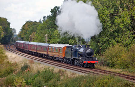 Steam train on a short excursion through woodlands with a fully loaded set of carriages Stock Photo - 10904142
