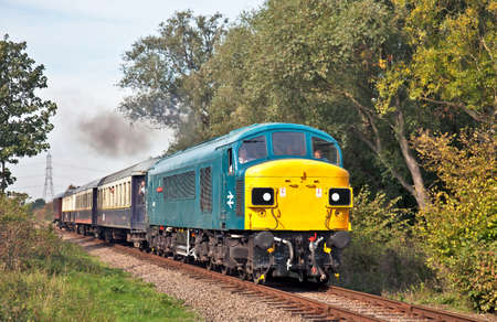 CASTOR, ENGLAND - OCTOBER 1: Preserved class 45 (45060) diesel locomotive, Sherwood Forester, passes Castor crossing during the Nene Valleys autumn diesel gala with a fully loaded set of carriages on October 1, 2011 at Castor. Stock Photo - 10868154