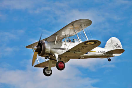 OLD WARDEN, ENGLAND - AUGUST 7: A veteran RAF Gloster Gladiator fighter plane demonstrates its maneuverability during a low flying aerial display on August 7, 2011 at the Shuttleworth summer air gala. Editorial