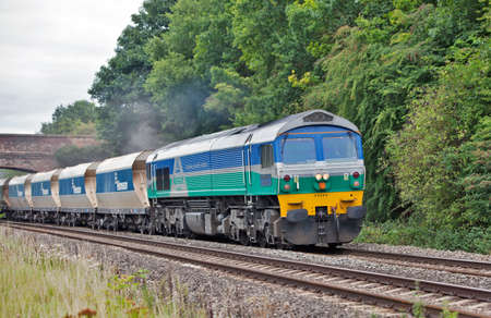 HUNGERFORD, ENGLAND-AUGUST 30: An aggregates freight train passes West bound through Hungerford park on August 30, 2011. These are specialist trains operated specifically for aggregrates distribution by a co-operative of aggregrates industry manufacturers Stock Photo - 10977349