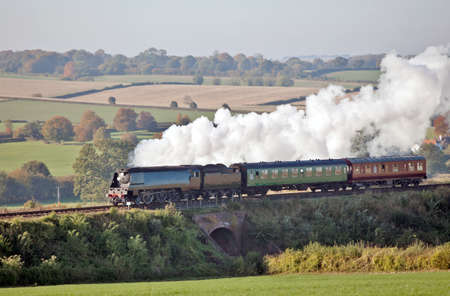 Steam train on a passenger service during the late autumn sun photo