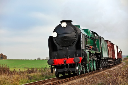 Steam loco taking a freight train through open countryside Stock Photo - 11409870