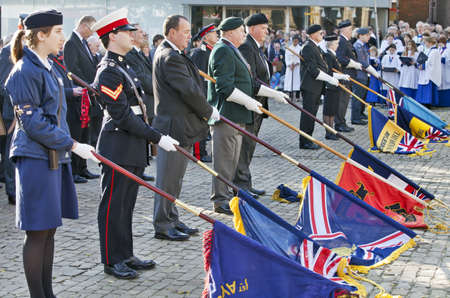 armistice: AYLESBURY, ENGLAND - NOVEMBER 13: Guard of Honour dip their banners in respect to the fallen soldiers at the Cross of Honour during the Armistice Parade on November 13, 2011 in Aylesbury Editorial