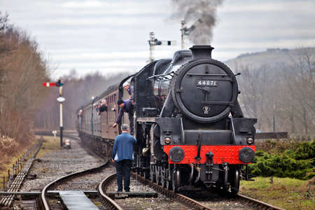 RAMSBOTTOM, ENGLAND - JANUARY 23: Black 5 steam locomotive, 44871, passes the token to the guard before entering the station platform area at the East Lancashire Railway Steam gala on January 23, 2011 at Ramsbottom