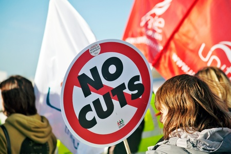 public sector: AYLESBURY, ENGLAND - NOVEMBER 30: A public sector worker carries her placard simply stating the message No Cuts to the proposed government pension changes on November 30, 2011 in Aylesbury Editorial