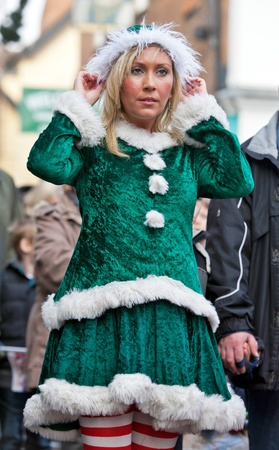 AYLESBURY, ENGLAND - NOVEMBER 20: A young woman dressed in Christmas elf costume takes a break before parading into the market square at the Christmas parade festival on November 20, 2011 in Aylesbury