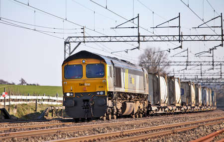 COW ROAST, ENGLAND - MARCH 23: Freight train carrying bulk liquid tanks passes north along the WCML on March 23, 2010 at Cow Roast. UK rail freight is growing rapidly where the largest freight trains may remove 160 HGV journeys from the road Stock Photo - 11887317