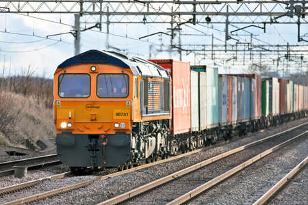 CHEDDINGTON, ENGLAND - JANUARY 19: A diesel intermodal freight train passes north through Hertfordshire on January 19, 2012 at Cheddington. UK rail freight is increasing YOY as a viable alternative to reduce road journeys throughtout the UK road network Stock Photo - 12201154