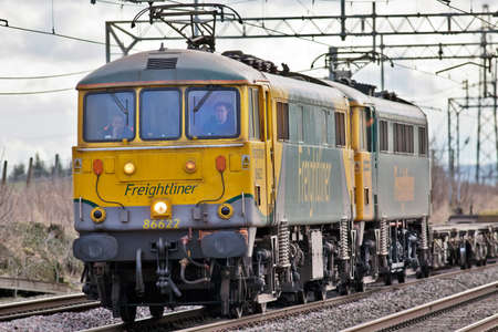 TRING, ENGLAND - JANUARY 19, 2012: Two class 86 electric locos pass northbound with an empty freight train. Nearly 50 years old examples of this class are now being exported for additional haulage power required on the Hungarian railway network. Stock Photo - 12201152
