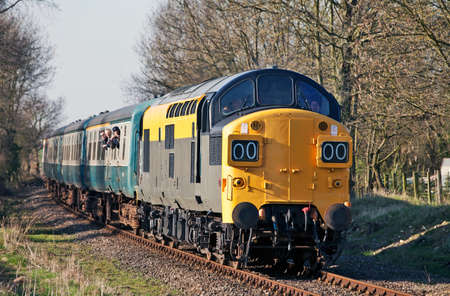 YAXLEY, ENGLAND - MARCH 19: An ex British Rail class 37 locomotive, now in Dutch railways livery, takes passengers on pleasure trips at the Mid Norfolk Railway spring diesel gala on March 19, 2011 at Yaxley Stock Photo - 12316216