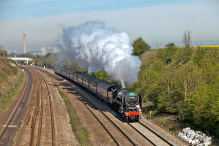 NORTH MORETON, ENGLAND - APRIL 7: BR std class 7 steam loco, Britannia, heads the Cathedrals Express through Didcot cutting on its inaugural tour as it re-enters mainline service on April 7, 2011 at North Moreton Stock Photo - 12316227