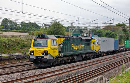 DUDSWELL, ENGLAND - JUNE 24: An American built class 70 heavy freight loco passes north with a semi intermodal freight train on June 24, 2011 at Dudswell. Class 70 locos are the newest freight units on the UK rail network. Stock Photo - 12316222
