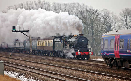NORTH MORETON, ENGLAND - FEBRUARY 12: Ex GWR mainline steam locomotive, Edward I, heads west on the express line passing a local diesel suburban train on February 12, 2012 at North Moreton. Stock Photo - 12316218