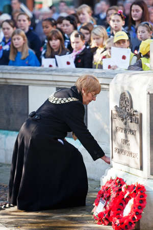 AYLESBURY, ENGLAND - NOVEMBER 13: Town Mayor & councillor of Aylesbury, Jenny Puddefoot, places a remembrance wreath at the Cross of Honour on Armistice Day on November 13, 2011 in Aylesbury. Stock Photo - 12469165