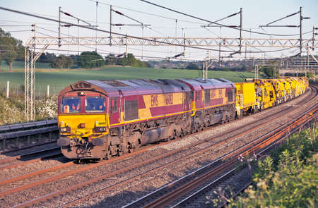 TRING, ENGLAND - MAY 21: An exceptionally long train of rail infrastructure vehicles passes northwards on the WCML on May 21, 2011 at Tring. EWS, now part of the German International operator DB Schenker Rail, is the largest single rail haulier in the UK Stock Photo - 12469171