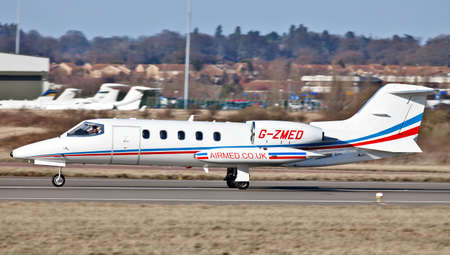 LUTON, ENGLAND - FEBRUARY 25: An Airmed Learjet lands at Luton airport with emergency medical equipment on February 25, 2012 in Luton. Airmed, an air ambulance service, operates 9 aircraft globally