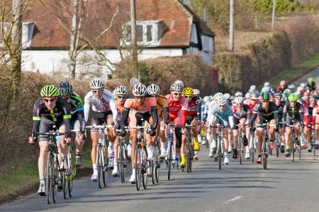 turn over: CLAYDON, ENGLAND - MARCH 10: Cyclists competing in the Roy Thame Cup prepare for a sharp left hand turn over a damp road surface on Lap 2 of the race on March 10, 2012 at Claydon.