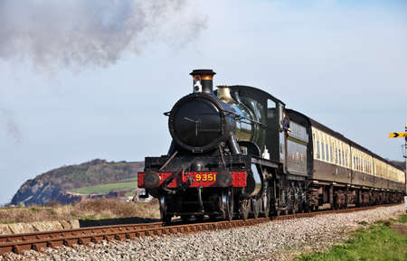 BLUE ANCHOR, ENGLAND - MARCH 23: Steam loco 9351 traveling adjacent to the coastline on the West Somerset Railway en route to Minehead at the spring WSR steam gala at Blue Anchor on March 23, 2012  Editorial