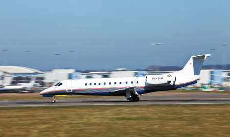LUTON, ENGLAND - MARCH 28: An Embraer Legacy 600 business jet lands at London Luton airport at Luton on March 28, 2012 Introduced in 2000 over 183 units have been sold at a unit price of $27.45Mn Stock Photo - 13140512