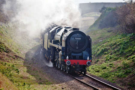 britannia: WATCHET, ENGLAND - MARCH 25: Steam loco Britannia takes an early Sunday morning  train through Watchet cutting en route to Minehead at the Spring WSR steam gala on March 25, 2012 at Watchet