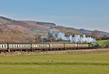 britannia: BICKNOLLER, ENGLAND - MARCH 23: Ex BR Pacific, Britannia, rounds Bicknoller curve en route to Bishops Lydeard at the West Somerset Railway spring steam gala on March 23, 2012 at Bicknoller Editorial
