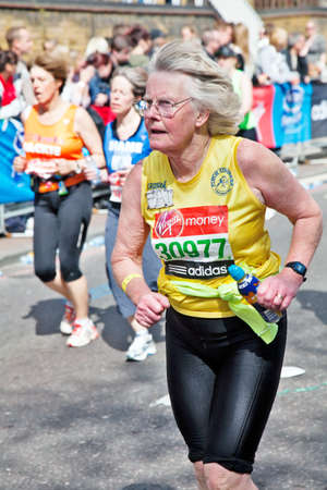 participants: LONDON - APRIL 22: One of the older female participants in the 2012 London marathon starts the climb uphill towards the 23 mile marker at Tower underground station on April 22, 2012 in London