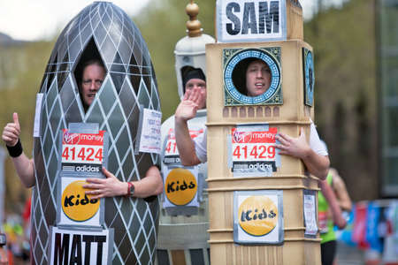 LONDON - APRIL 22: Three fun runners in the 2012 London marathon, wearing costumes of prominent London buildings, pause for a breath as they reach the 23 mile mark on April 22, 2012 in London Stock Photo - 13575926