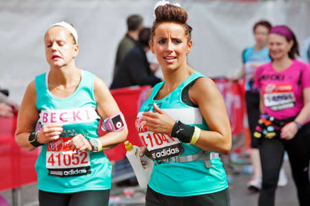 LONDON - APRIL 22: Two female runners participating in the London 2012 marathon pass the 22 mile marker with only 4.2 miles left to complete the course on April 22, 2012 in London Stock Photo - 13575921