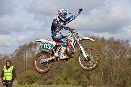 CULHAM, ENGLAND - MAY 5: Moto-X rider Ben Milward punches the air mid jump as he approaches the finish line in first place at the Culham Park vintage moto-X gala on May 5, 2012 at Culham Stock Photo - 13714846