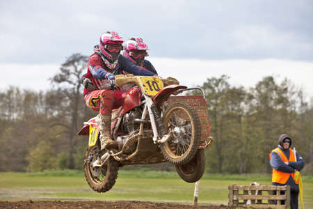 CULHAM, ENGLAND - MAY 5: An unnamed motorcycle & sidecar team leave the ground at speed while negotiating a steep uphill section at the Culham Park vintage moto-X event on May 5, 2012 at Culham Stock Photo - 13714833