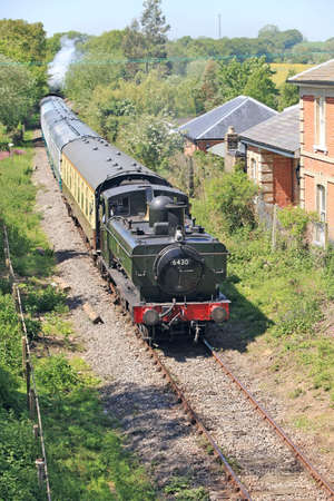 weald: ONGAR, ENGLAND - MAY 25: Pannier tank 6430 leads the first passenger train service from North Weald to Ongar since the lines closure from mainline service in 1994 on May 25, 2012 at Ongar Editorial