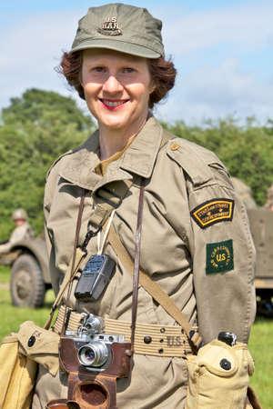 reenactor: Portsmouth, Inglaterra - 03 de junio: Una mujer militar de re-enactor vestido como un corresponsal de prensa del Ej�rcito de EE.UU. de la �poca de 2 � Guerra Mundial posa para la c�mara en la feria Overlord Miltary el 3 de junio de 2012 a Portsmouth Editorial