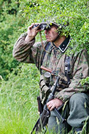 reenactor: Portsmouth, Inglaterra - 03 de junio: Un militar de re-enactor vestido con uniforme alem�n de paracaidistas del ej�rcito se refugia en un simulacro de batalla recreaci�n en la feria Overlord Militar el 3 de junio de 2012 a Portsmouth Editorial