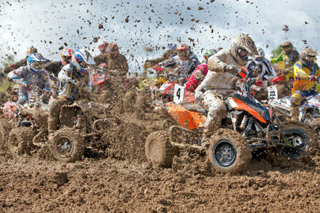 mx: ENSTONE, UK - JUNE 24: Riders participating in the Nora MX British quad bike championship hit the first corner at speed, creating a cloud of liquid mud, during Race 1 of 3 on June 24, 2012 at Enstone