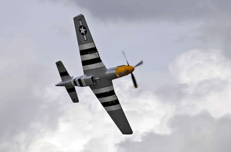 ABINGDON, UK - MAY 6: A veteran WW2 P51 Mustang fighter aircraft gives an aerobatic display in stormy skies for the watching public at the Abingdon airshow on May 6, 2012 at Abingdon