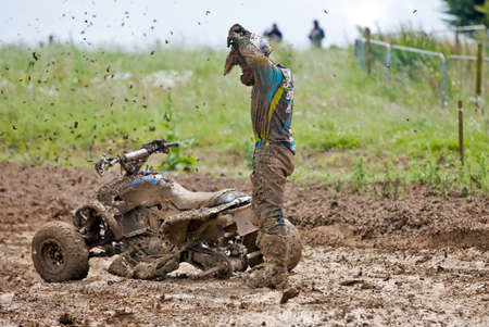 mx: ENSTONE, UK - JUNE 24: An unnamed rider at the Nora MX British quad bike championship loses a rear wheel taking a tight left hand corner in thick mud on June 24, 2012 at Enstone