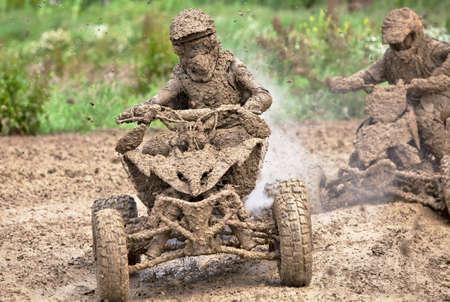 mx: ENSTONE, UK - JUNE 24: An unnamed rider participating in the British Nora MX Pro quad championships rounds a tight corner with his quad leaking water and covered in mud on June 24, 2012 at Enstone.  Editorial