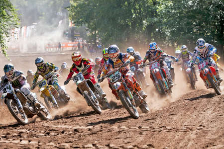 acu: HOPTON, UK - JULY 29: The final race of the day, combined MX1 & MX2 classes head towards corner one at Hawkstone Park during the ACU UK MX chanpionships, in a cloud of dust on July 29, 2012 at Hopton  Editorial