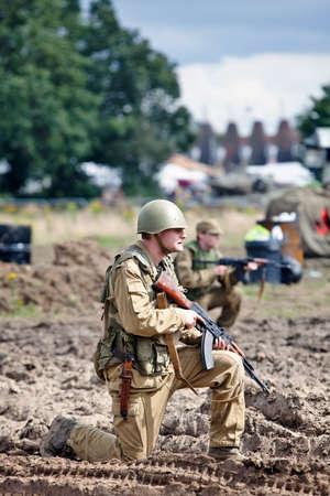 reenactor: BELTRING, Reino Unido - 19 de julio: Un nuevo enactor vestido con uniforme del ej�rcito ruso se prepara para atacar a un mu�eco de madera casa ocupada por Afgan re-enactors en la Guerra y la Paz espect�culo el 19 de julio de 2012 a las Beltring