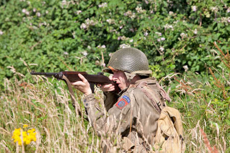 crouches: BELTRING, UK - JULY 19: A WW2 US soldier re-enactor crouches in long grass while demonstrating sniper tactics to the public at the War & Peace show on July 19, 2012 at Beltring  Editorial