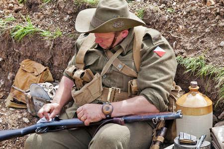reenactor: PORTSMOUTH, Reino Unido - 3 de junio: Una nueva enactor de la sociedad de la FIA limpia su fusil Lee Enfield en una zanja cambio marca en el Sal�n del Overlord Militar el 3 de junio de 2012 a Portsmouth